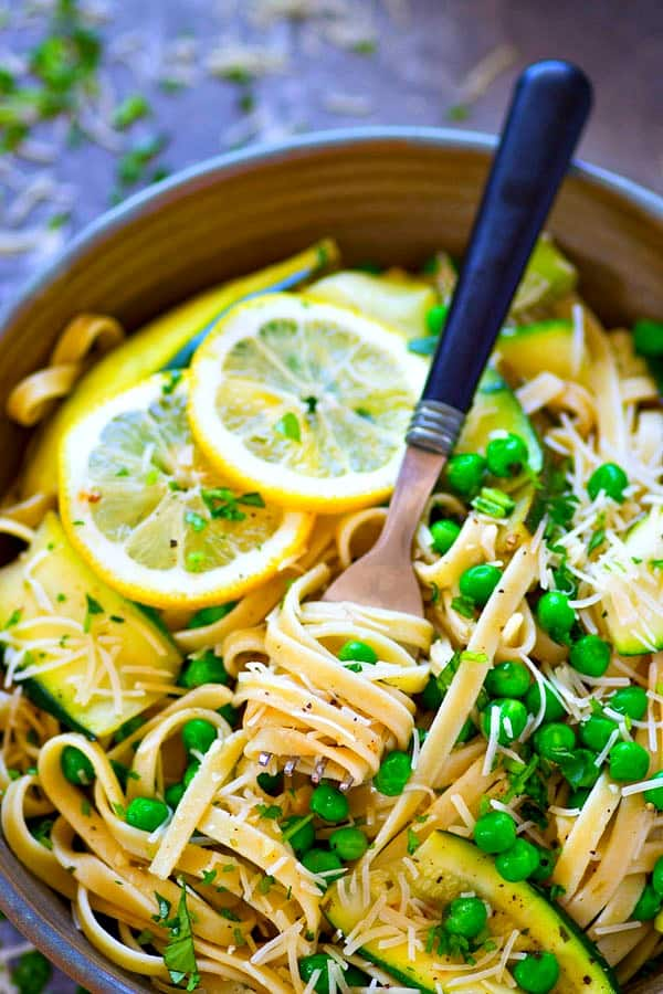 This lemon Parmesan fettuccine with tons of tender zucchini ribbons and sweet peas is the only thing you need to up your pasta night game! The lemon garlic butter sauce is life-changing.