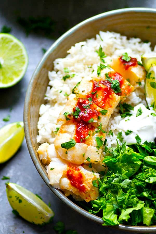 Melt-in-your-mouth tender white fish is marinated in a chipotle yogurt marinade then seared to perfection and piled high into these fish taco rice bowls with tons of zippy mango salsa!