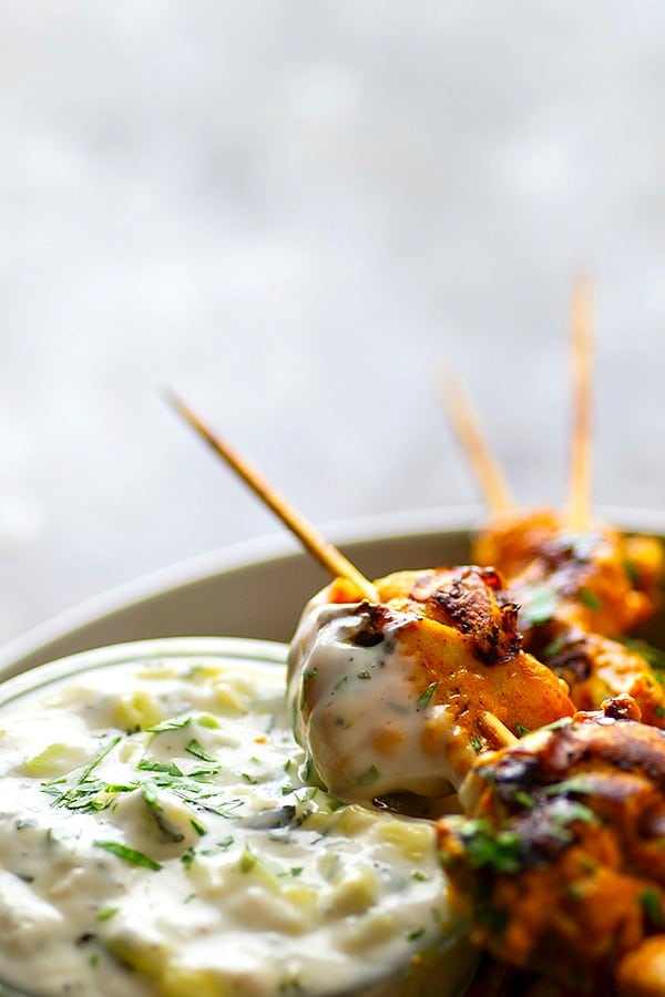 Hands down the BEST grilled tandoori chicken skewers you will ever throw on the grill this summer. The secret is in the SUPER flavorful long marinade and homemade tzatziki sauce.