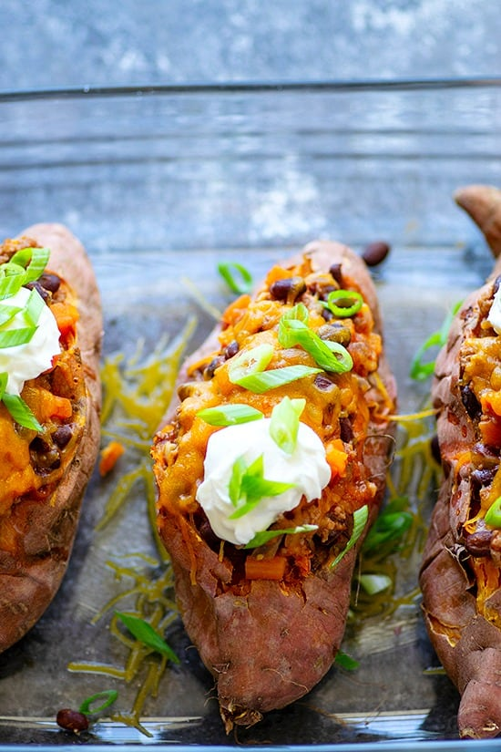Turkey Chili Twice-Baked Sweet Potatoes - the PERFECT healthier way to get your chili fix! Soft sweet potatoes are packed with flavorful turkey chili, tons of cheese, and all your favorite chili toppings.