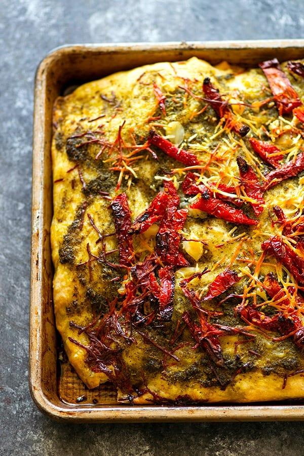 Roasted Garlic Sun-Dried Tomato Pesto Focaccia - Tangy sun-dried tomatoes and nutty roasted garlic deliver MASSIVE flavors in this incredibly soft pesto focaccia! Making it overnight makes it SO easy to prepare.