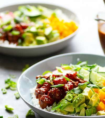 Spicy Ginger Mango Salmon Poke Bowls - A spicy ginger sauce, sweet fresh mango, and tons of veggie goodness are piled into these healthy salmon poke bowls that are SUPER easy to make at home for a fraction of the restaurant cost!