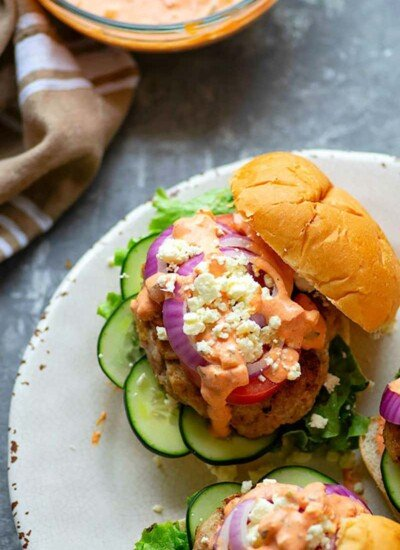 Grilled chicken burgers are piled high with fresh Greek toppings and a creamy red roasted red pepper tzatziki sauce for an incredibly flavorful Greek twist on burgers!