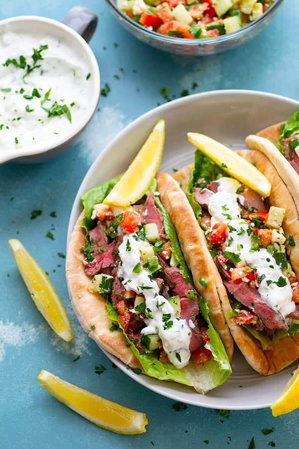 Grilled to perfection and piled high with a fresh cucumber feta salsa and lots of homemade tzatziki sauce, these grilled steak gyros are a fresh summer twist on the classic sandwich!