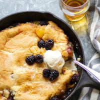 Classic peach blackberry cobbler is the ultimate dessert ode to summer! Flavorful brandy is tossed in the fruit filling with even more brushed on top hot from oven. Serve this beautiful cobbler with plenty of vanilla ice cream!