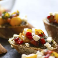 Tender roasted red peppers coupled with flavorful pesto and creamy goat cheese are an incredible flavor trio in this goat cheese bruschetta that's super impressive, incredibly easy, and perfect for entertaining!