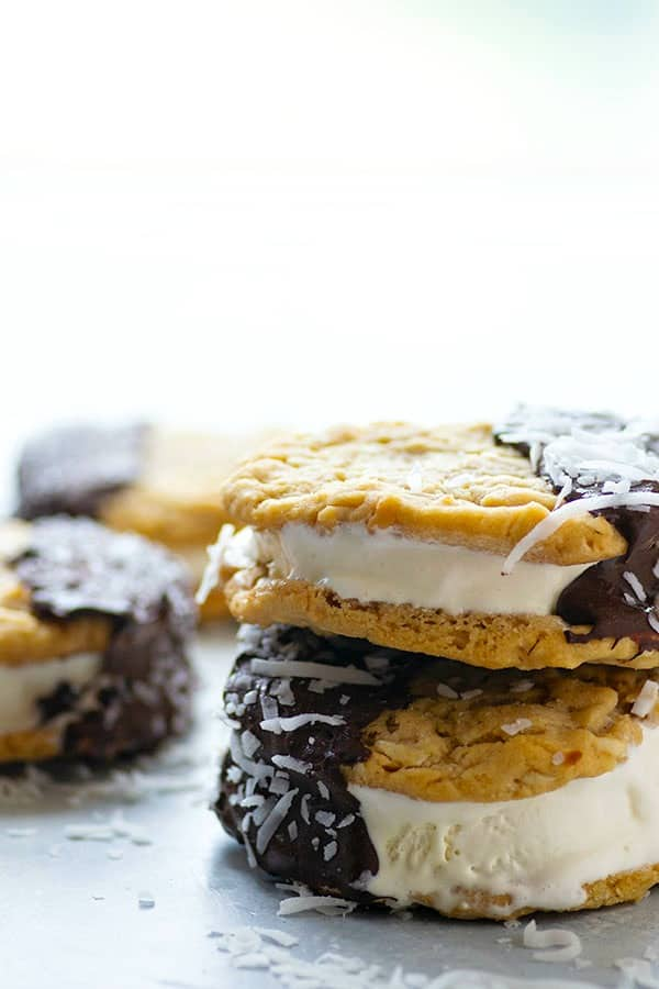 Coconut peanut butter cookies are the perfect base to these peanut butter ice cream sandwiches that feature a rich chocolate coating and a creamy vanilla ice cream filling.---they're impossible to resist!