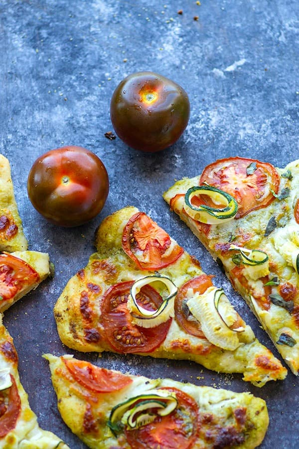 Tender zucchini, flavorful pesto, and juicy summer heirloom tomatoes make for the perfect summer-style pesto flatbread!