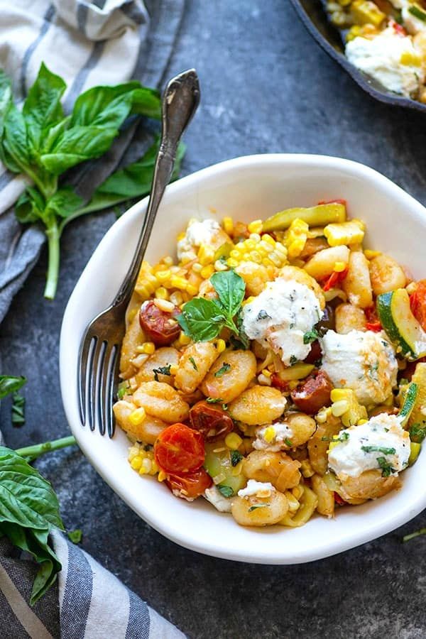 Crispy pan fried gnocchi is loaded with sweet charred corn, juicy cherry tomatoes, and creamy herbed ricotta for an easy 30-minute dinner just brimming with summer goodness!