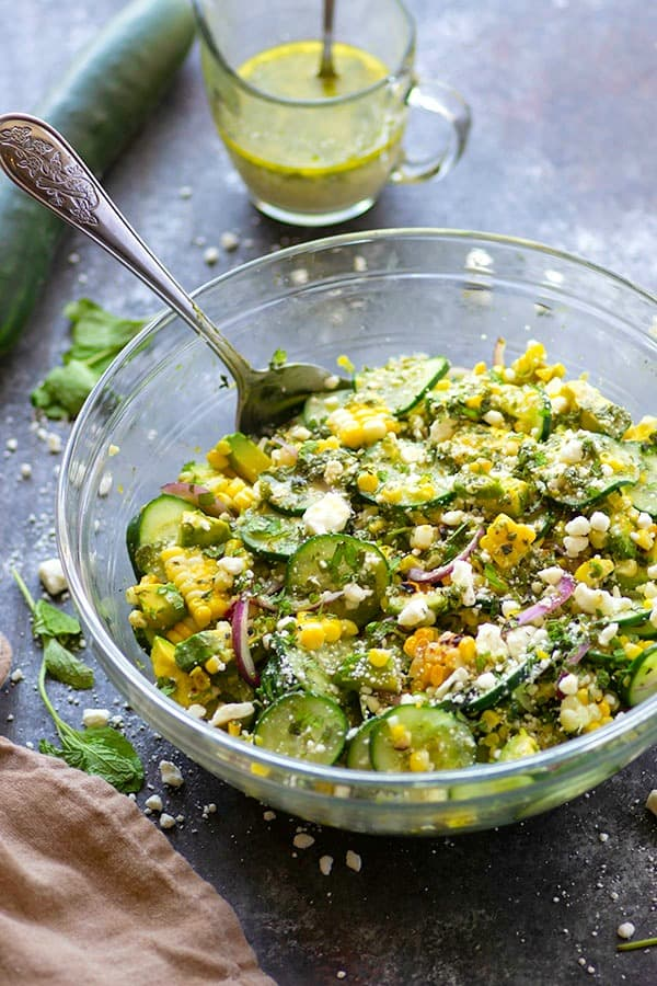 Charred sweet corn, silky avocado, and crisp cucumbers are tossed in a flavorful feta mint dressing for the most incredible summer twist on cucumber salad!
