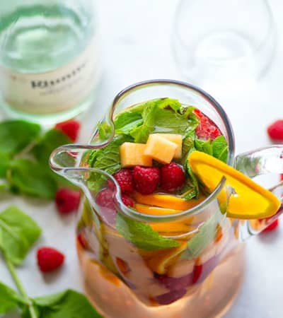 Sweet moscato sangria is livened up with the addition of fresh cantaloupe, tangy raspberries, and refreshing mint leaves.