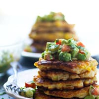 Perfectly crispy and golden sweet corn fritters are spiced up with roasted green chiles and an incredibly flavorful tomatillo avocado salsa piled on top!