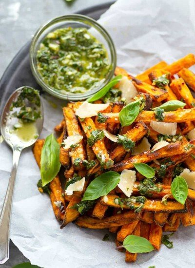 Perfectly crispy baked sweet potato fries are drizzled in a flavorful basil chimichurri sauce and topped with Parmesan cheese shards for a healthier appetizer or side dish!