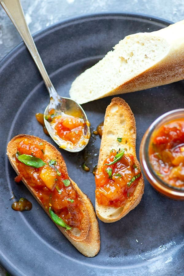 Fresh basil and juicy sweet peaches add the perfect summer touch to this heirloom tomato jam! Wonderful spread on a toasted baguette and an incredible condiment for a charcuterie board.