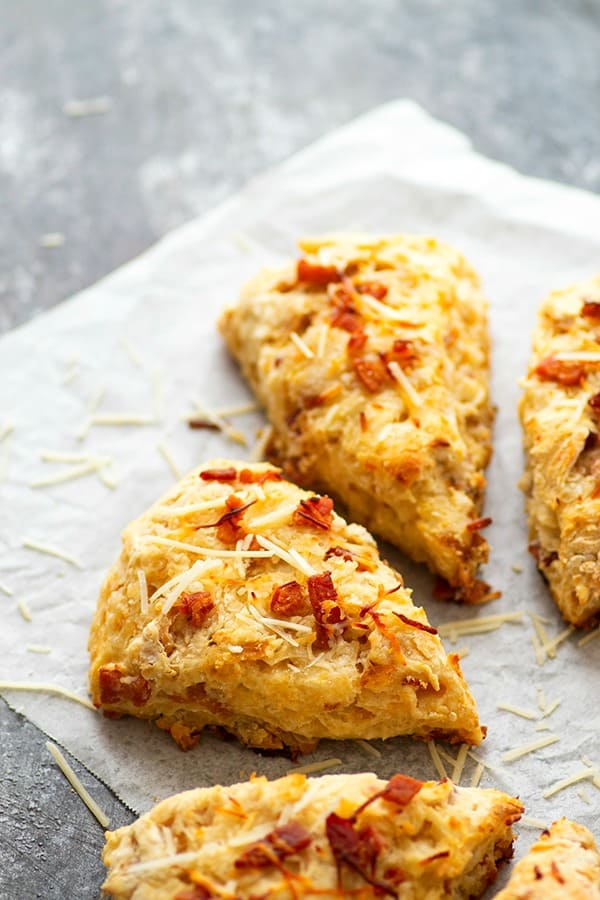 Sharp Asiago cheese and flavorful caramelized onion bits make for incredible savory flavors in these flaky bacon scones! They bake up in only 30 minutes and are a perfect savory breakfast pastry OR dinner side dish.