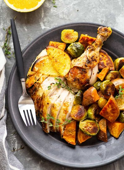 Roasted with a ginger orange butter and served with tender sweet potatoes and brussels sprouts, this orange roast chicken is a simple, yet impressive way to make roast chicken for a holiday dinner!