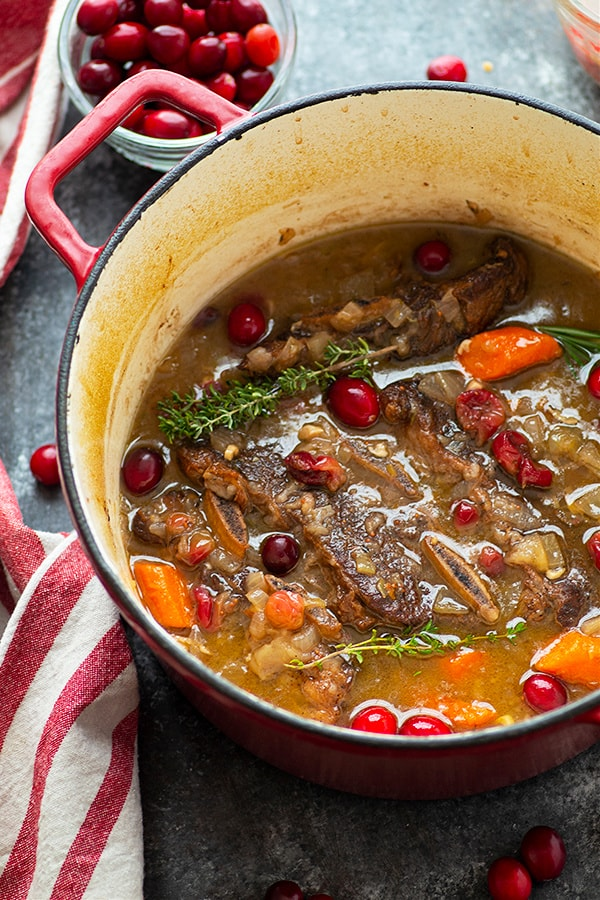Flavorful apple cider and tart cranberries take these apple cider braised beef short ribs to the next level! So easy to make and super impressive for dinner entertaining.