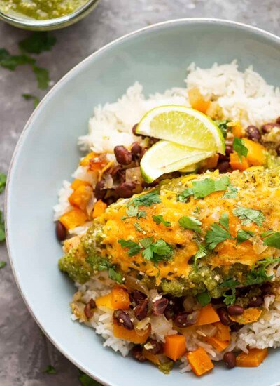 Baked in a fresh homemade salsa verde and flavorful sweet pepper black beans, this salsa verde chicken is ready in under an hour and fantastic served over hot rice!