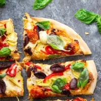 This Mediterranean baked feta pizza is a spin off of the viral TikTok pasta and loaded with artichoke hearts, olives, and the classic feta tomato sauce!