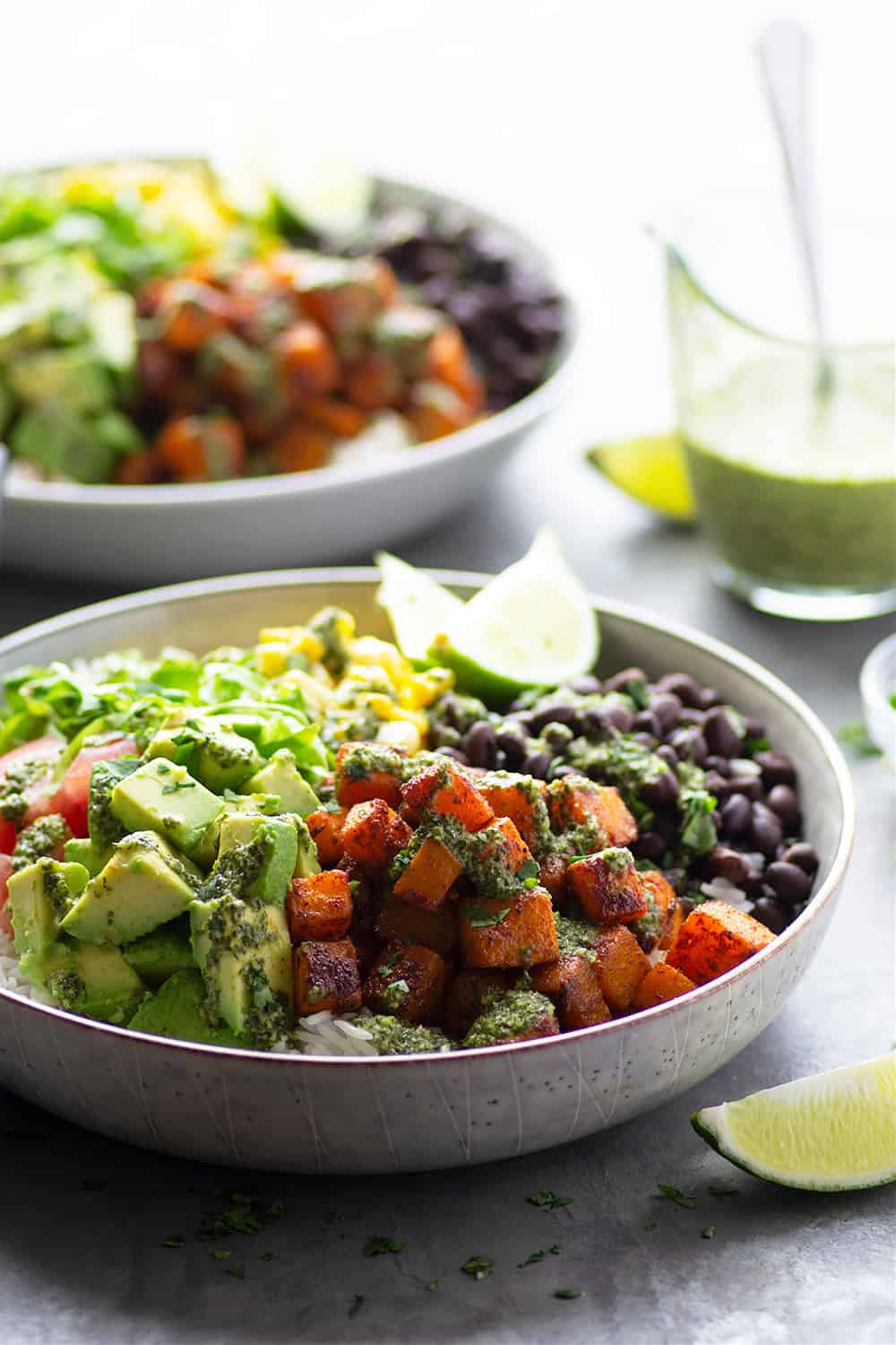 Blackened butternut squash burrito bowls are piled high with all the fixins' and a flavorful fresh mojo sauce for a healthy take on burrito bowls! Completely vegetarian AND vegan!