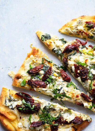 Piled high with a creamy spinach artichoke spread, tangy sun-dried tomatoes, and crumbled feta, this spinach artichoke flatbread is definitely a stand-out appetizer or lighter dinner!