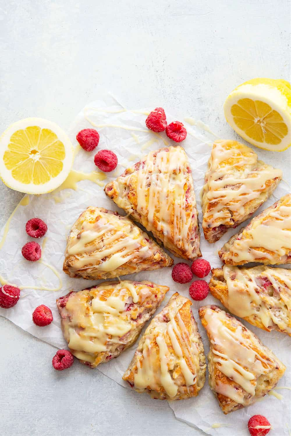 Perfectly flaky and loaded with juicy raspberries and tangy lemon flavor, these lemon raspberry scones are glazed in a rich white chocolate glaze and a beautiful addition to any brunch!