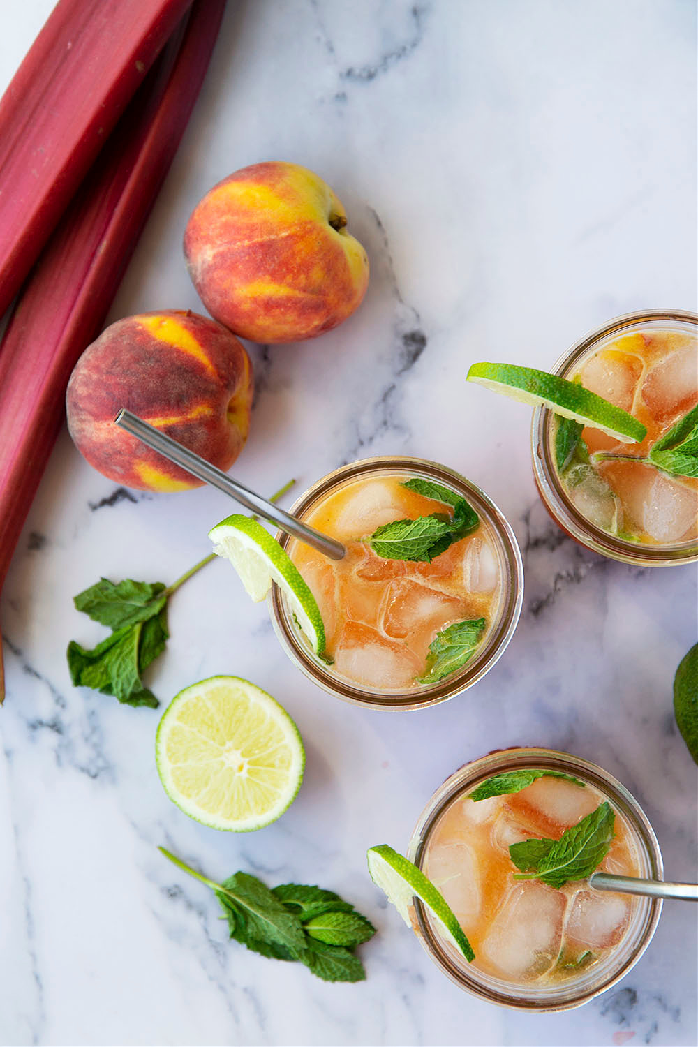 Rhubarb peach bourbon smash is a refreshing summer cocktail with juicy peaches, firey bourbon, and a tangy homemade rhubarb syrup.