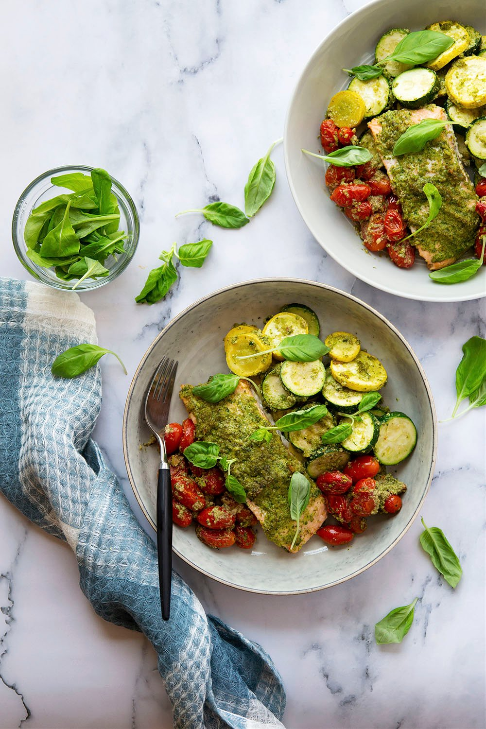 Baked entirely on one sheet pan and smothered in flavorful arugula pesto, this bursting tomato pesto salmon and zucchini is the perfect weeknight dinner to use up an abundance of veggies!