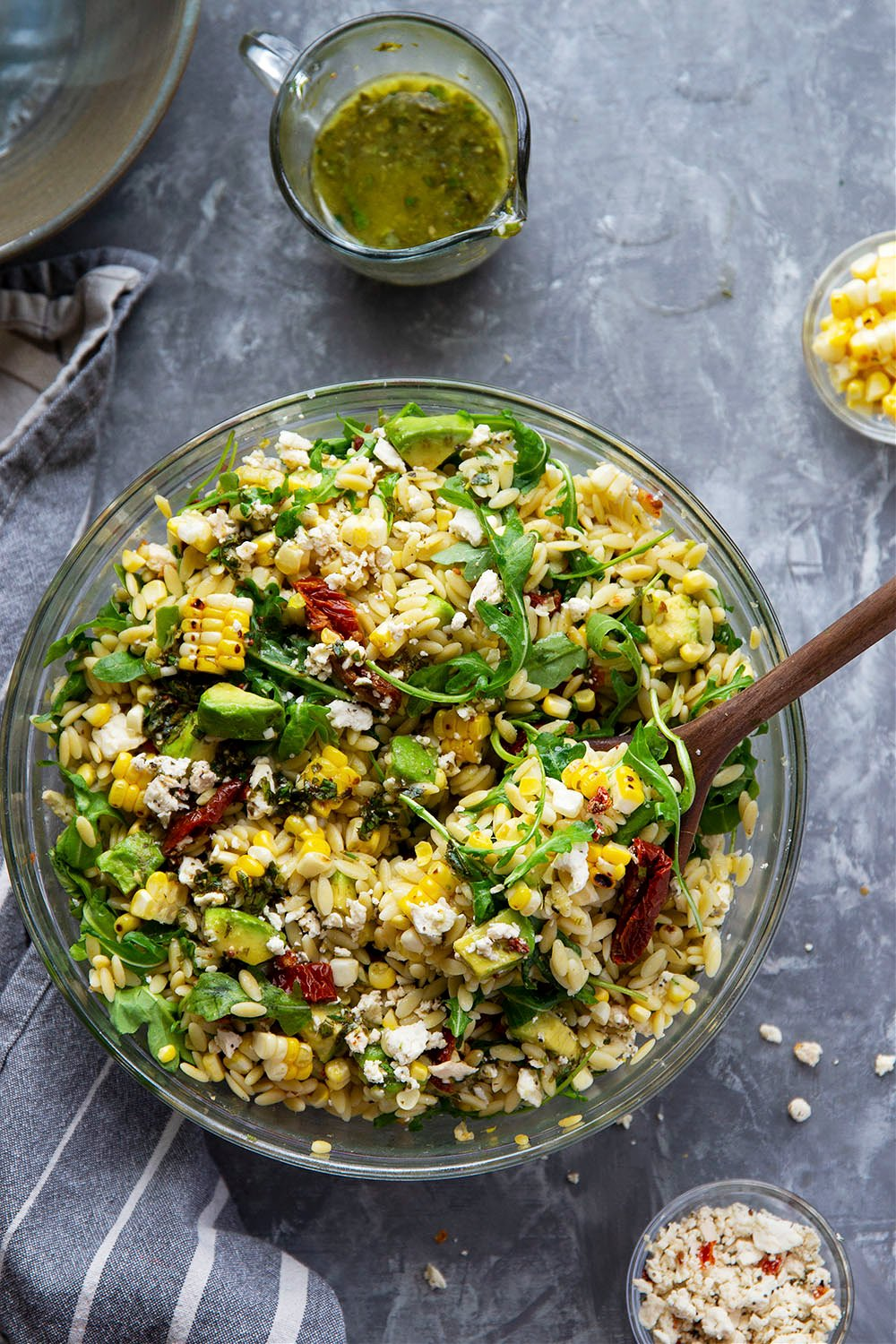 This sun-dried tomato orzo salad is packed with charred sweet corn, silky avocado, tangy feta, and tossed in a flavorful lemon herb vinaigrette. - perfect for a lunch salad or cookout side!