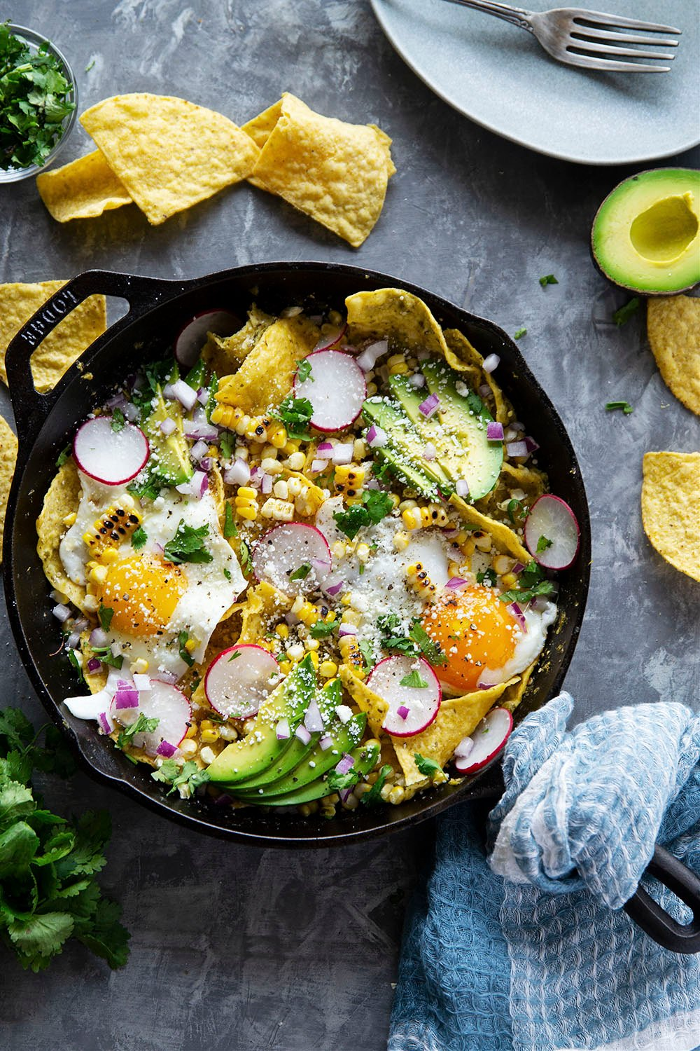 Classic chilaquiles verdes features crispy corn chips smothered in a homemade salsa verde and topped with charred sweet corn, fried eggs, and all the extra toppings you desire!