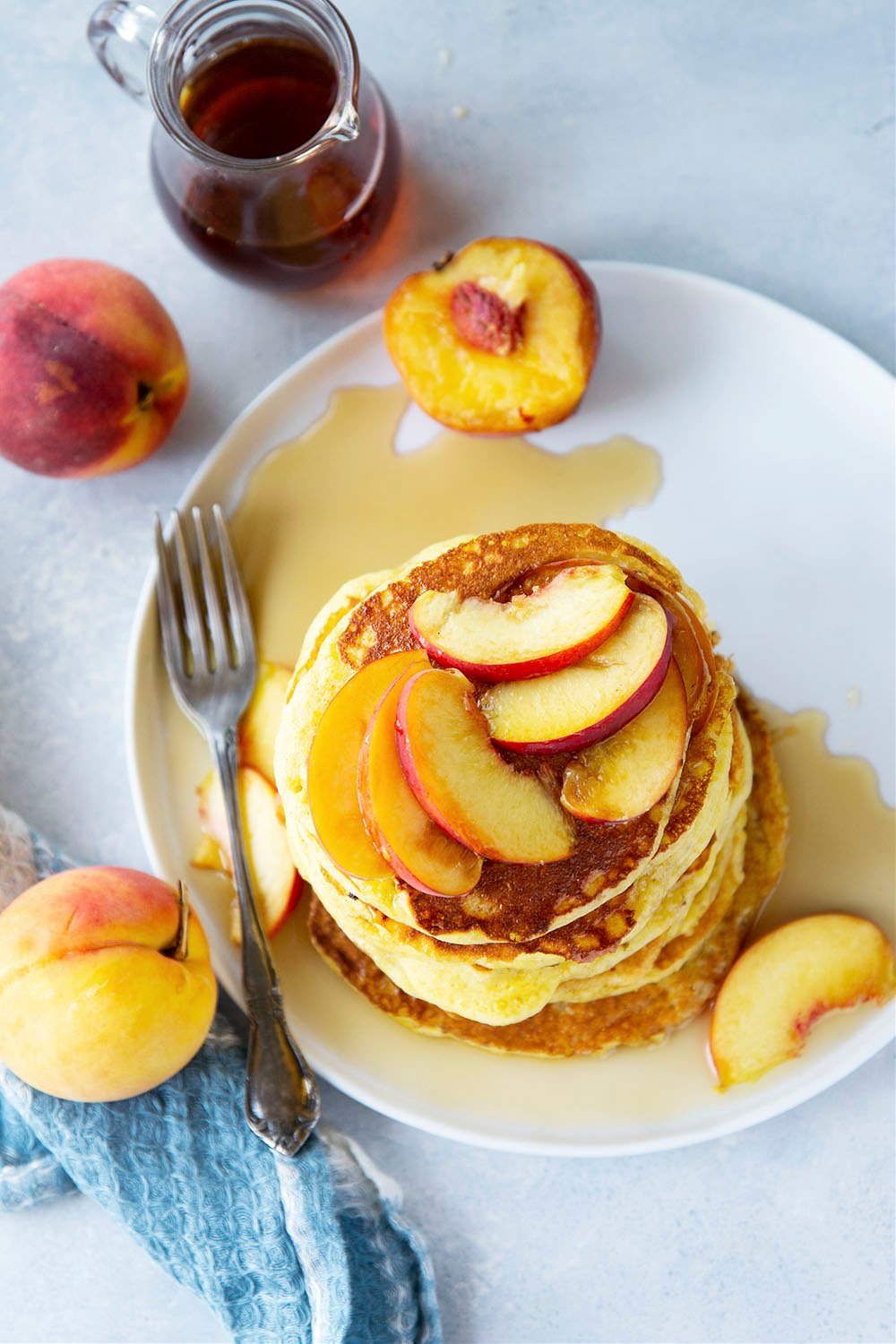 Juicy summer peaches and hearty cornmeal star in these tender, fluffy cornmeal peach pancakes that are a perfect stack for summer!
