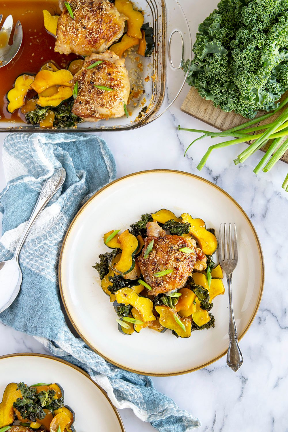 Honey sesame chicken thighs are roasted with tender acorn squash and kale in a flavorful honey sesame sauce for an easy dinner made in less than an hour!